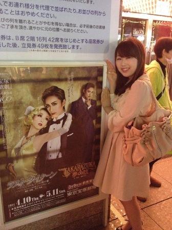 Ms. Ai Furukawa beside the poster of Takarazuka revue at the Tokyo Takarazuka theater.